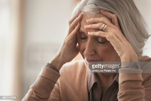 senior caucasian woman holding her forehead - one senior woman only stock pictures, royalty-free photos & images