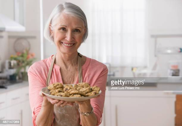 Senior Caucasian woman holding plate of cookies