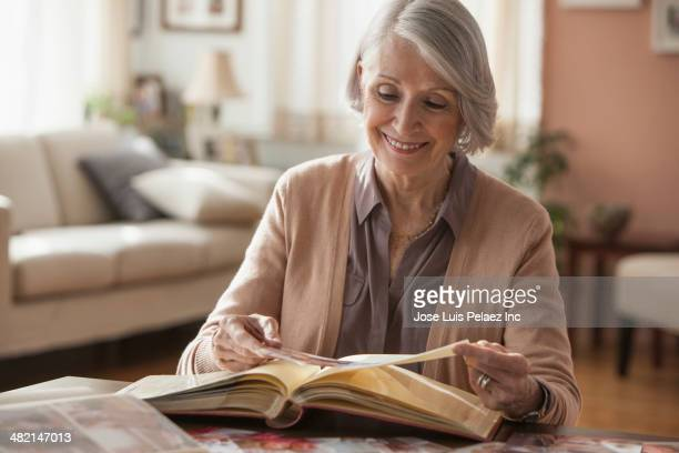 Senior Caucasian woman looking through photo album