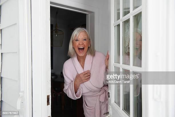 Senior Caucasian woman opening door in bathrobe