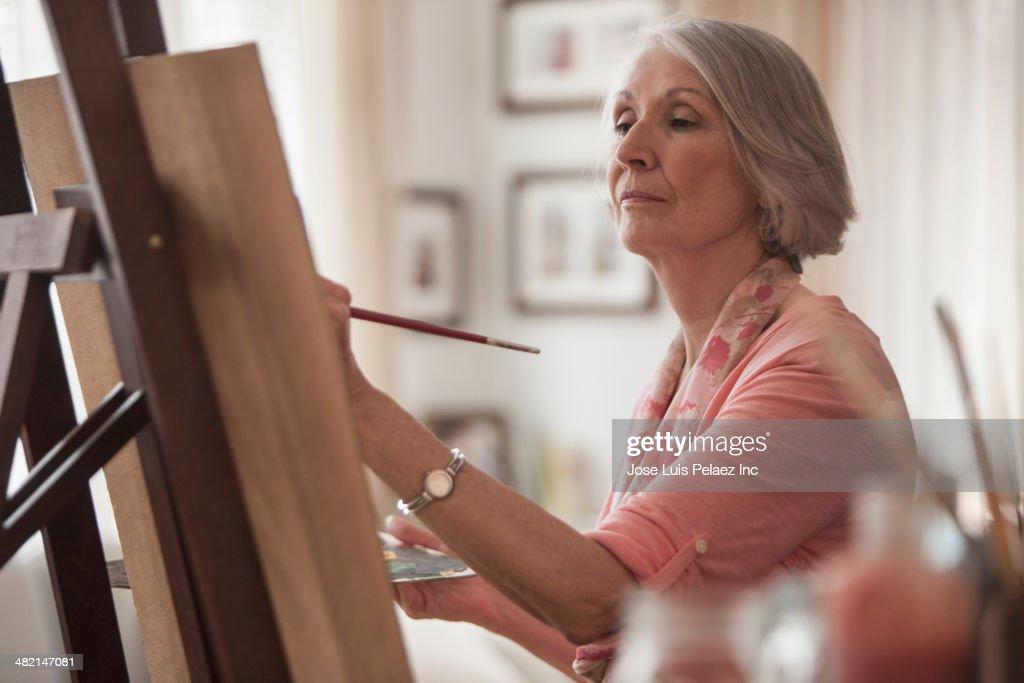 Senior Caucasian woman painting at easel : Stock Photo