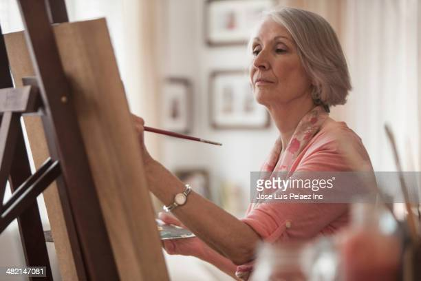 senior caucasian woman painting at easel - actieve ouderen stockfoto's en -beelden