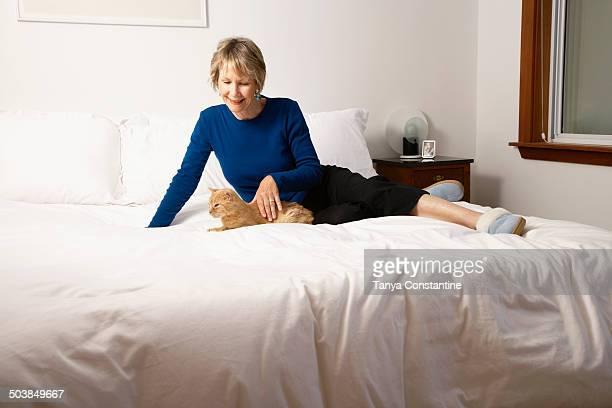 Senior Caucasian woman petting cat on bed