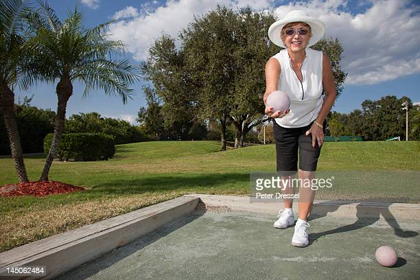 Senior Caucasian woman playing bocce ball