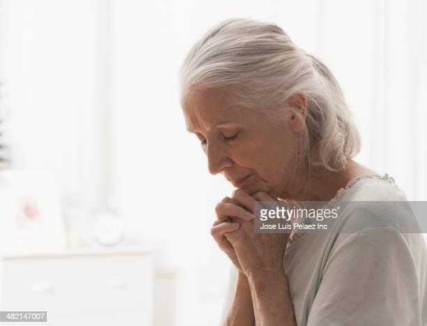senior caucasian woman praying - rezando - fotografias e filmes do acervo