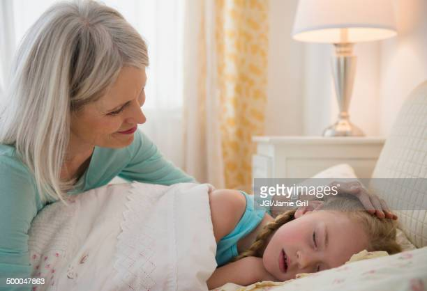 Senior Caucasian woman putting granddaughter to bed