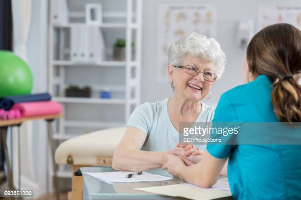 Senior Caucasian woman receives hand massage from physical therapist