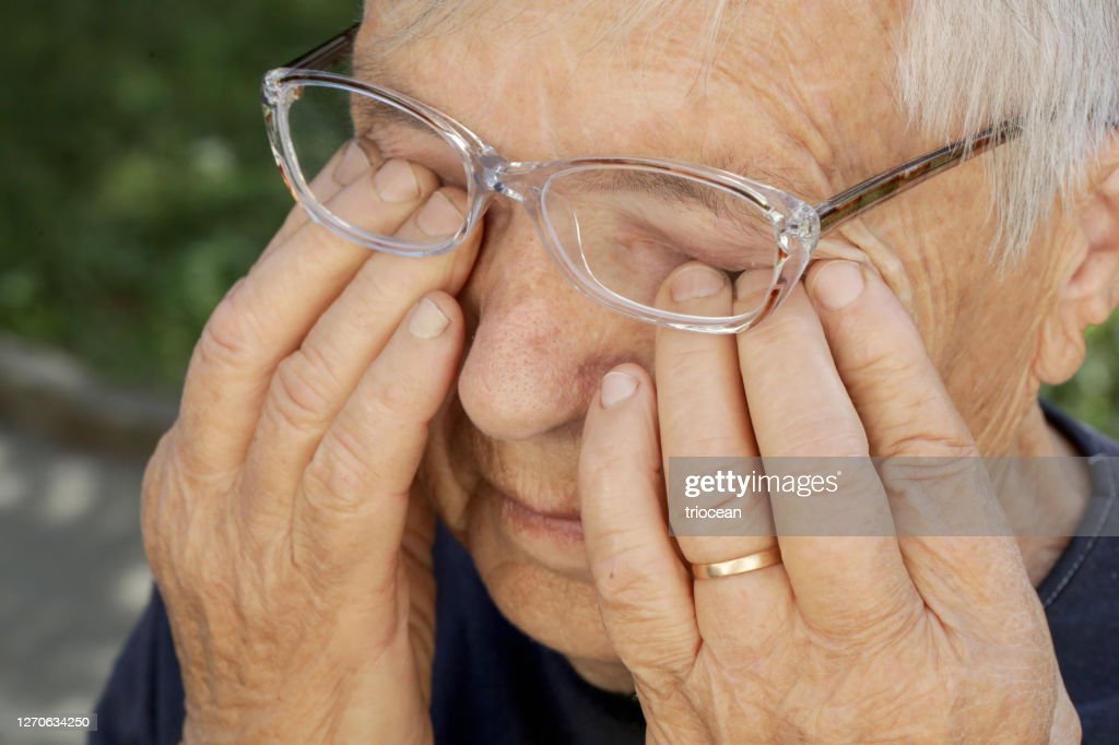 Senior caucasian woman rubbing her eyes under eyeglasses : Stock Photo