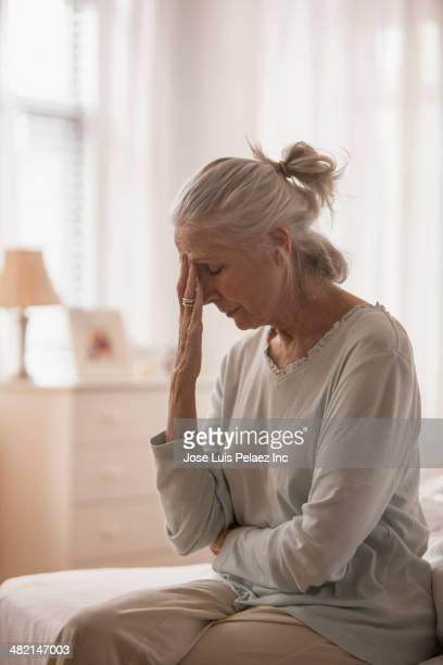 Senior Caucasian woman rubbing her forehead on bed