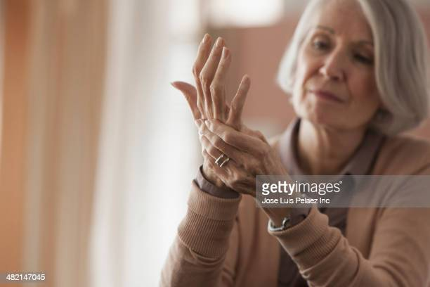 senior caucasian woman rubbing her hands - human body part stock-fotos und bilder
