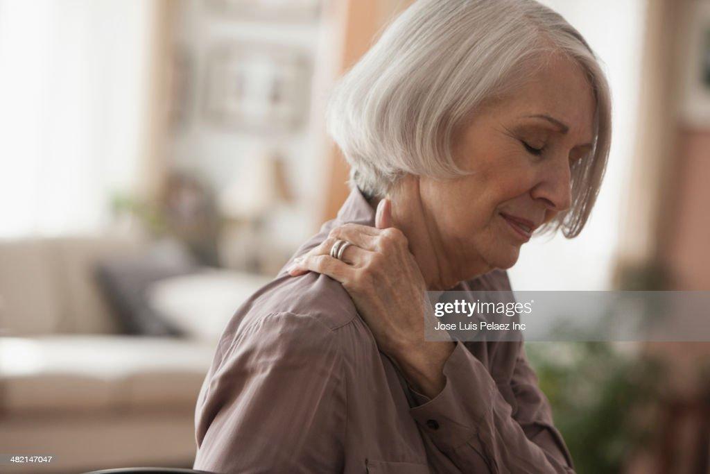 Senior Caucasian woman rubbing her shoulder : Stock Photo