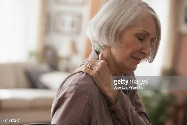 senior caucasian woman rubbing her shoulder - pijn stockfoto's en -beelden