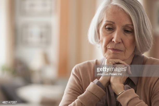 senior caucasian woman with chin in hands - seniore vrouwen stockfoto's en -beelden
