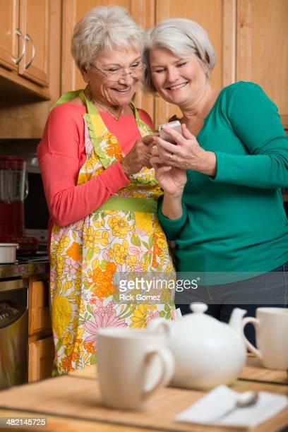 Senior Caucasian women using cell phone in kitchen
