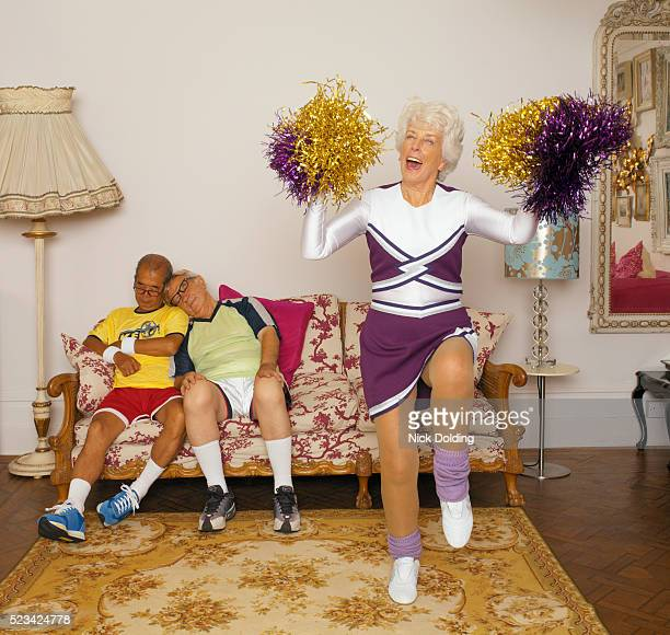 senior cheerleader with two men sleeping on couch - cheerleaders stock pictures, royalty-free photos & images