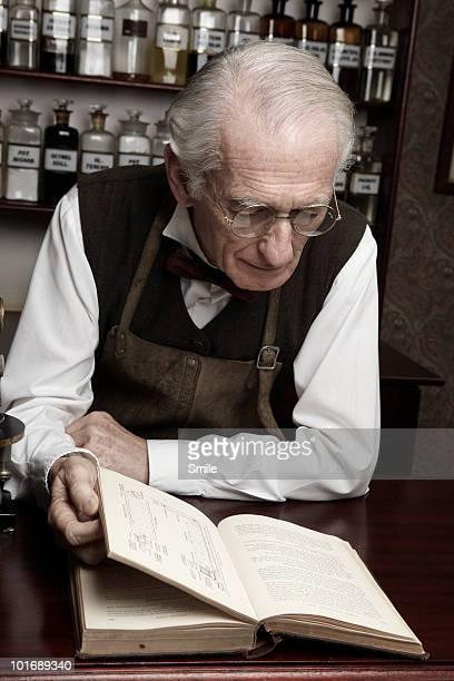 Senior chemist reading a book