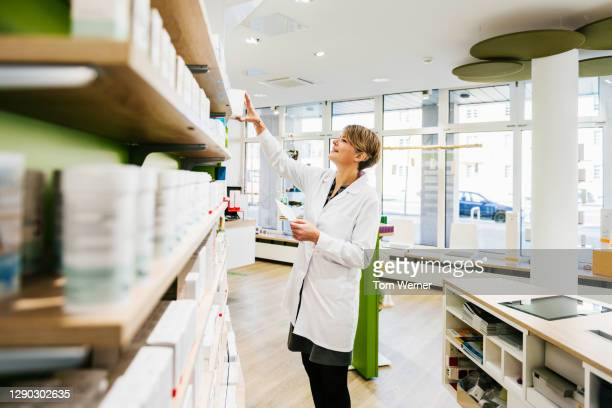 senior chemist stocking shelves in pharmacy - healthcare stock pictures, royalty-free photos & images