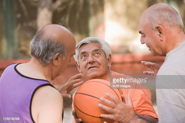 Senior Chilean men playing basketball together