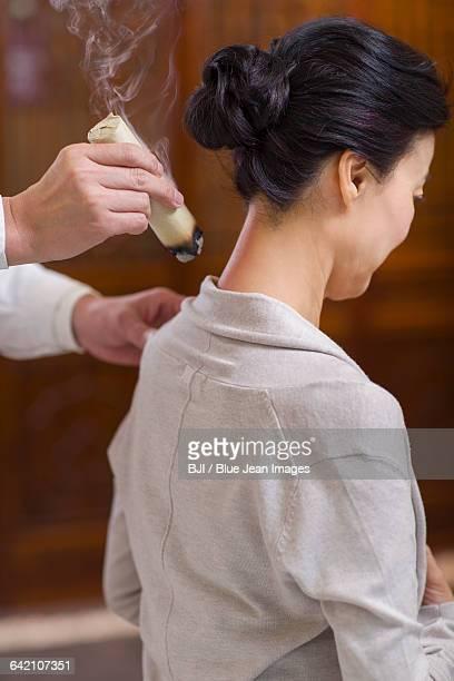 Senior Chinese doctor giving moxibustion