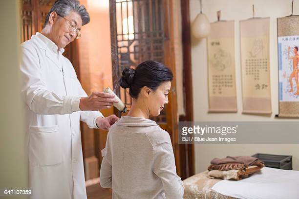 Senior Chinese doctor giving moxibustion