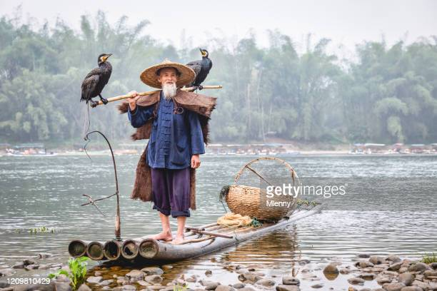senior chinese fisherman on traditional wooden raft li river, china - asian style conical hat stock pictures, royalty-free photos & images
