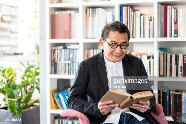 senior chinese man reading a book - man holding book stock pictures, royalty-free photos & images