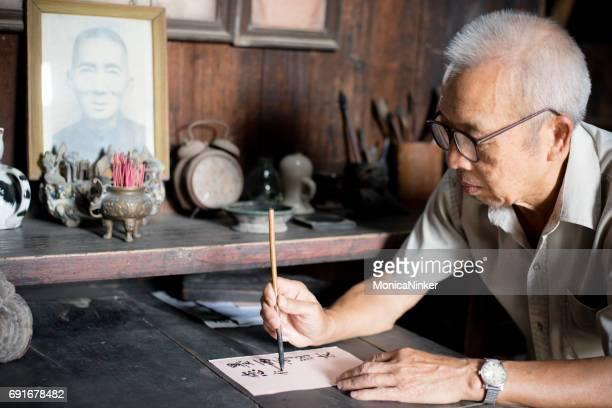 Senior Chinese man writing characters
