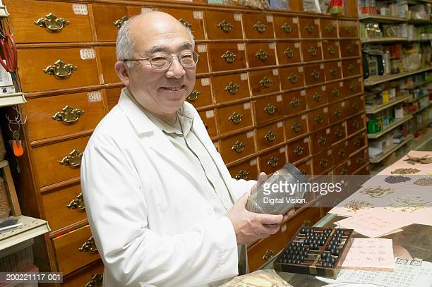 Senior Chinese-herbalist behind counter in store, smiling, portrait
