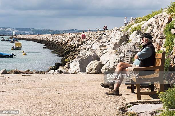 Senior Citizen and the harbour wall at Bixham in Devon