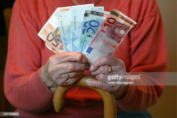 Senior citizen counting Euro banknotes