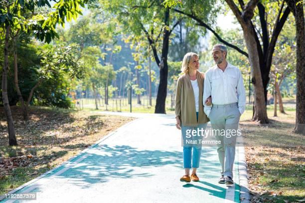 senior citizen couple taking a walking in a park during summer morning. seniors couple spend time in public park together. - aktiver lebensstil stock-fotos und bilder