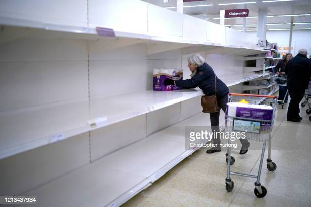 A senior citizen gets the last pack of toilet rolls at Sainsbury's Supermarket on March 19 2020 in Northwich United Kingdom A queue of approximately...