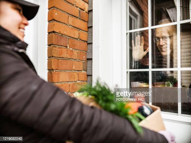 covid-19,ロックダウン中の高齢者宅配食品配達 - 隣人 ストックフォトと画像