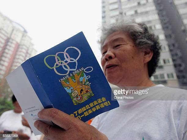 A senior citizen learns English words at a residential area during a community activity in Haidian District on August 29 2005 in Beijing China The...