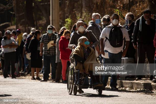 Senior citizen pushes a senior woman in a wheelchair to the Tenancingo de Degollado sports center to receive the Covid-19 vaccine on March 9, 2021 in...