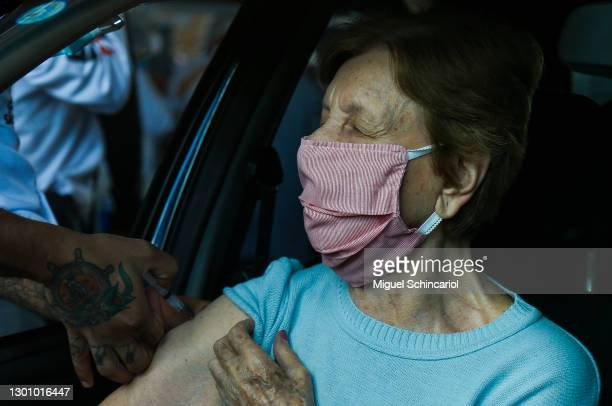 Senior citizen receives a dose of the CoronaVac vaccine at a drive-thru vaccination center set up at the Pacaembu Stadium on February 8, 2021 in Sao...