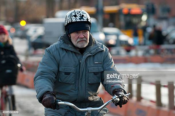 senior citizen rides a bicycle - cycling helmet stock photos and pictures