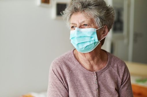 A senior citizen sits alone on her bed with a respirator or surgical mask 1213437805