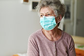 A senior citizen sits alone on her bed with a respirator or surgical mask