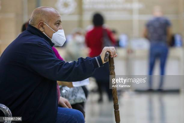 Senior citizen wearing a protective facemask and keep a social distance from each other while queuing inside ASAN service in Baku on May 20 2020 in...