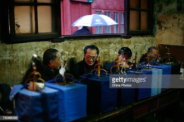 Senior citizens enjoy tea with their bird cages put aside at a Laohuzao teahouse at an alleyway January 23, 2007 in Shanghai, China. Laohuzao is a...