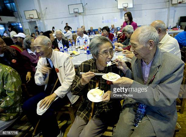 Senior citizens share a piece of golden wedding cake during a collective celebration of their golden wedding anniversary on September 12 2008 in...
