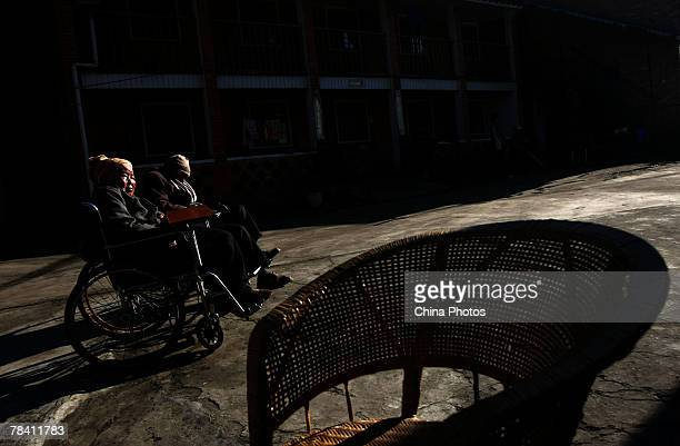Senior citizens sit in wheelchairs in the yard of Happy Times Nursing Home on December 12 2007 in Kunming of Yunnan Province China Twothirds of the...