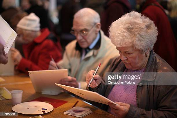 Senior citizens take part in a water colour painting session at The Retirement Show at Manchester Central on March 19, 2010 in Manchester, United...