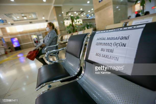 Senior citizens wearing a protective facemask and keep a social distance from each other while queuing inside ASAN service in Baku on May 20 2020 in...