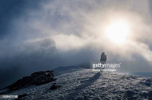 senior climber on a mountain ridge. - white jacket stock photos and pictures