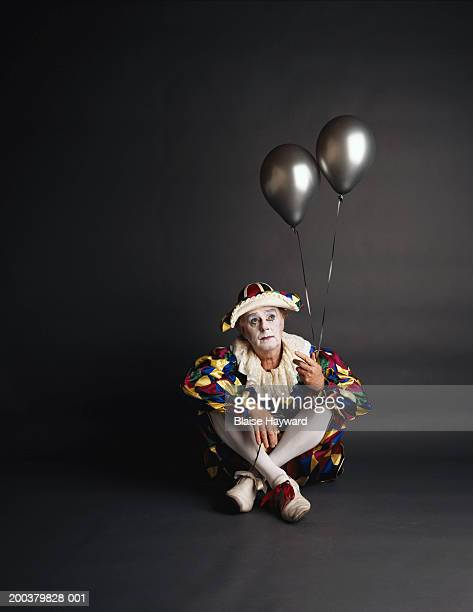 Senior clown holding silver ballons