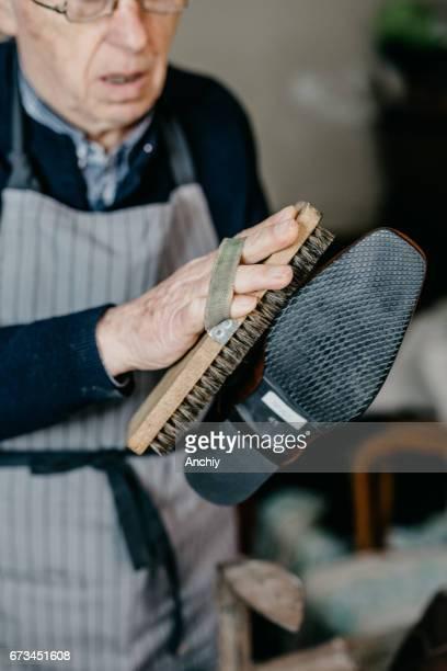 Senior cobbler is polishing a shoe