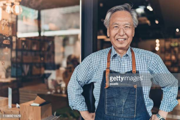 senior coffee shop owner - arms akimbo stock pictures, royalty-free photos & images