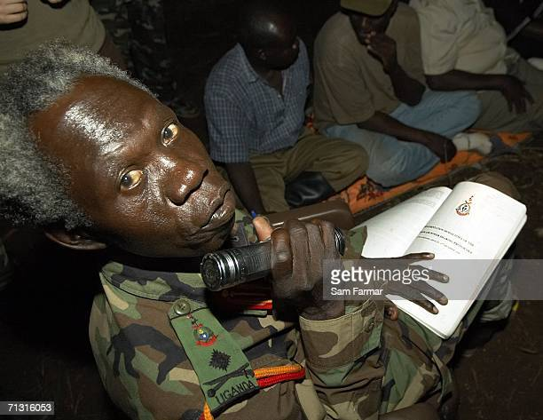 Senior commander of the Ugandan rebel group the Lord's Resistance Army, Vincent Otti shines a torch on an LRA document during a rare appearance in...